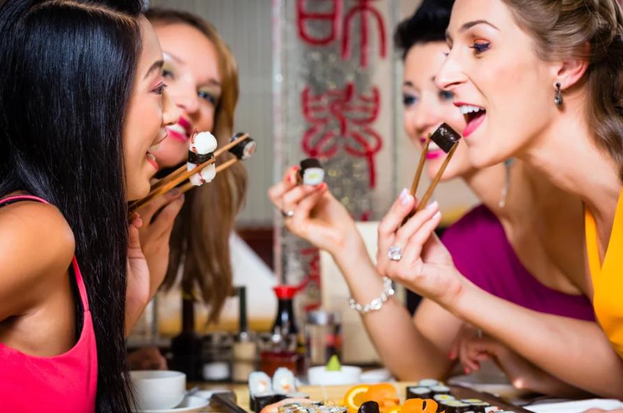 Дівич-вечір у ресторані: дівчата із задоволенням їдять суші та роли